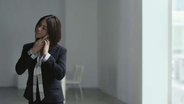 A business woman talks on her cell phone in a large office building Royalty-free stock video