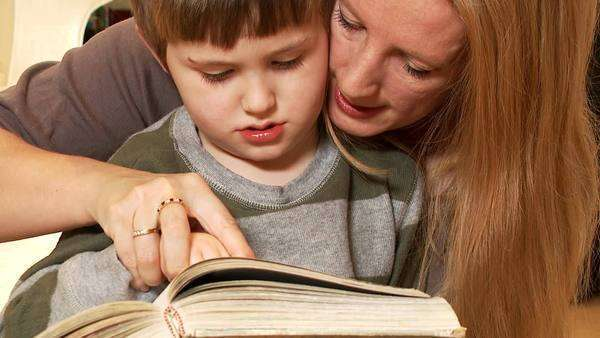 A cute young boy concentrates as his mother teaches him to read, close-up Royalty-free stock video