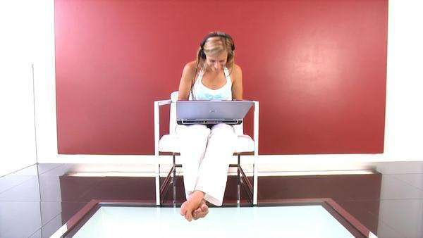 Attractive young woman listening to music through headphones as she works on her laptop Royalty-free stock video