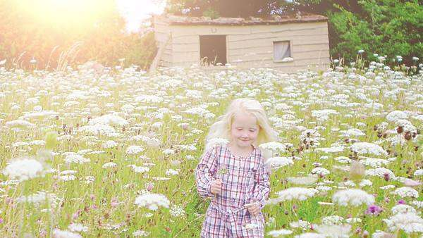 Little girl running through field of wild flowers, slow motion Royalty-free stock video