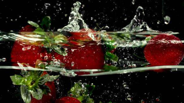 fresh strawberry fruit dropped into water shot in super slow motion with the Sony FS700 high speed camera Royalty-free stock video