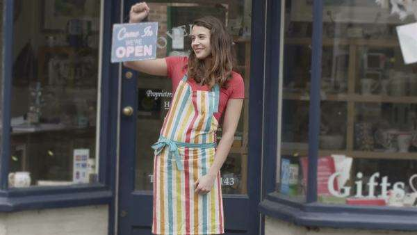 A happy and excited female shopkeeper stands outside of her small independent shop to welcome potential customers. She is holding an 'open' sign and wearing a colorful apron. Royalty-free stock video