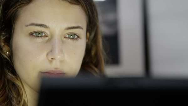 Close up of a very tired young woman who is working on a computer late into the night. She is over-worked and it is easy to see the emotional strain on her face. Royalty-free stock video