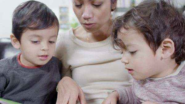 A mother reads a bedtime story to her 2 young sons and helps them to learn how to read. In slow motion. Royalty-free stock video