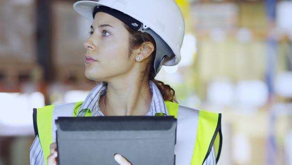 An attractive female warehouse employee wearing high visibility clothing and a hard hat is working on a digital tablet and checking stock levels. Other employees can be seen working in the background Royalty-free stock video