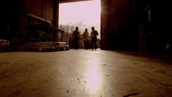 Atmospheric sepia toned clip of workers going about their business in a warehouse or storage facility. Sunlight streams into the area through the open shutter doorway. Low angle. Royalty-free stock video