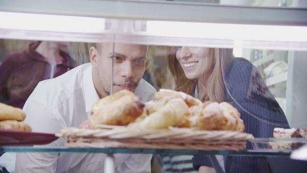 Happy attractive young couple choosing fresh pastries at the bakery counter. Royalty-free stock video