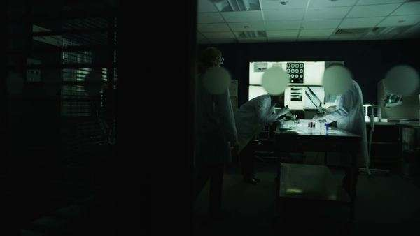 Team of scientists or researchers working in a dark laboratory are discussing their work. As seen from outside the window looking in. In slow motion. Royalty-free stock video