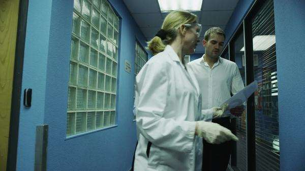 Workers at a medical or scientific research facility chat together as they approach the laboratory. In slow motion. Royalty-free stock video