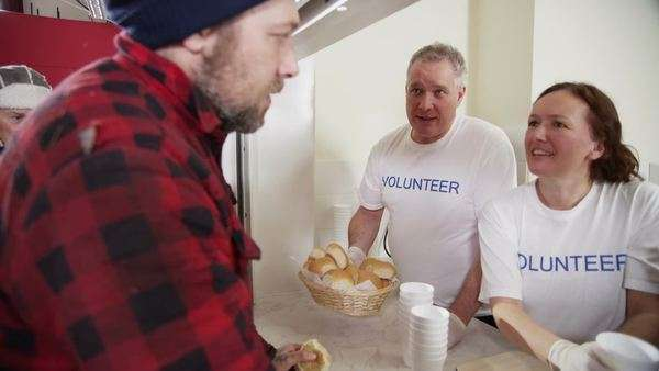 Friendly And Caring Voluntary Workers In A Soup Kitchen Help To Feed The  Homeless And The
