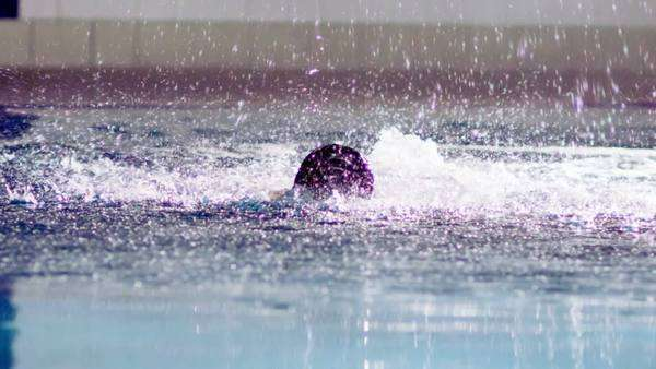 Powerful professional female swimmer in training is doing the butterfly stroke and coming up for air. In slow motion. Royalty-free stock video