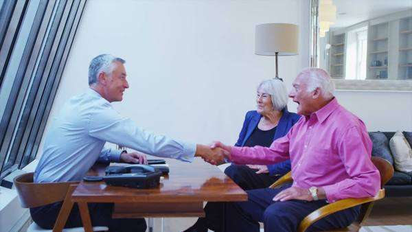 Cheerful senior couple in discussion with their financial advisor. Royalty-free stock video