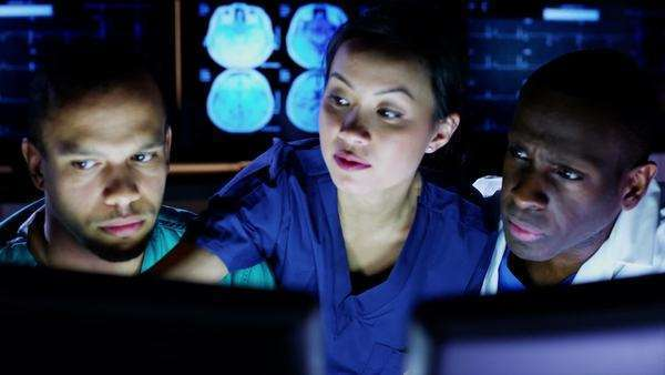 Mixed ethnicity group of medical professionals working late at night are looking at a computer screen and discussing what they see. Royalty-free stock video