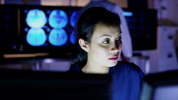 Beautiful Asian medical professional working late at night in a room full of computer screens. Royalty-free stock video
