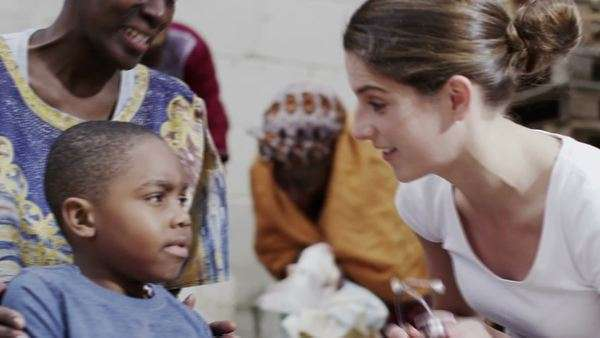 A medical worker from a charity organisation lets a little boy use her stethoscope to listen to her heartbeat. In slow motion. Royalty-free stock video