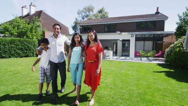 Portrait of happy young Asian family, standing in the garden of their contemporary home in the summertime. Royalty-free stock video