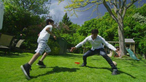 Cute young Asian boy playing soccer with his father in the garden on a bright summer day. In slow motion. Royalty-free stock video