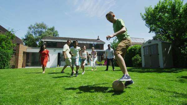 Happy mixed ethnicity group of friends and family playing sports and having fun in the garden on a summer day. In slow motion. Royalty-free stock video