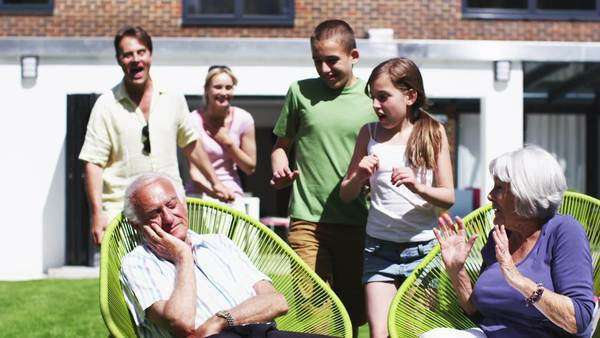 Three generations of a family spending time together in the garden at home. Grandpa pretends to be sleeping to give everyone a surprise. In slow motion. Royalty-free stock video