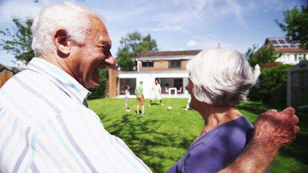 Loving senior couple embrace as they watch the rest of their family playing together in the garden at home. In slow motion. Royalty-free stock video