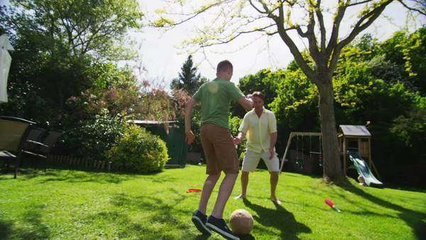 Active young boy playing soccer with his father outdoors on a bright sunny day. In slow motion. Royalty-free stock video
