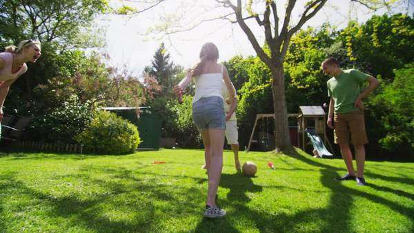 Active young girl shows off her soccer  skills as her family watch, outdoors on a bright sunny day. Royalty-free stock video