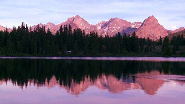 The Rocky Mountains are perfectly reflected in an alpine lake at sunset. Royalty-free stock video