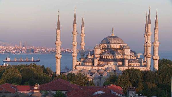 The Blue Mosque in Istanbul, Turkey at dusk with cargo ship background. Royalty-free stock video