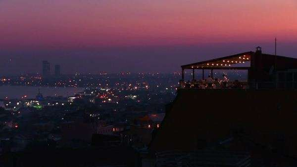 People eat dinner at a rooftop restaurant overlooking Istanbul, Turkey at dusk. Royalty-free stock video