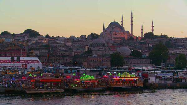 Colorful boats bob in the water at dusk in front of a mosque in Istanbul, Turkey. Royalty-free stock video