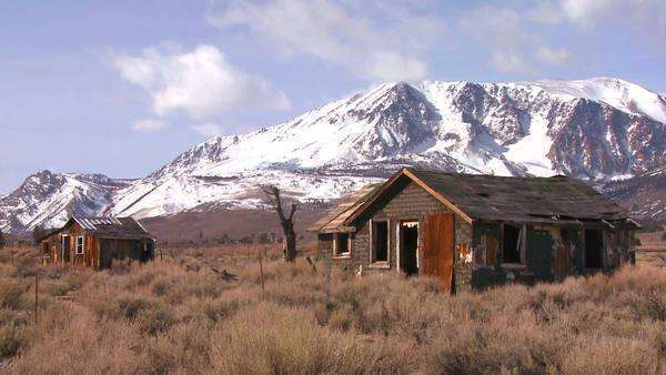 Abandoned settler cabins with the snow-capped Sierra Nevada mountains with the sun shining through clouds. Royalty-free stock video