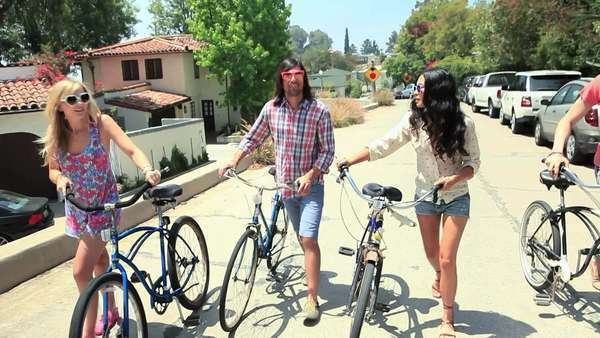 Friends pushing bicycles down a road on vacation Royalty-free stock video