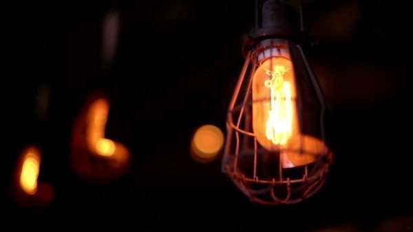 Close-up of dim lights hanging from a ceiling in wire cages. Royalty-free stock video