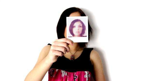 Woman holds up a polaroid, which develops and shows her face Royalty-free stock video