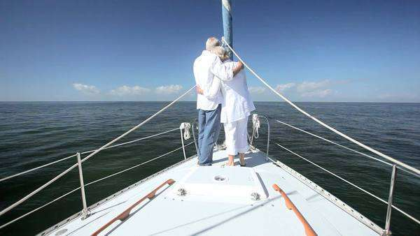 Contented retired couple enjoying  healthy outdoor lifestyle aboard their luxury sailing yacht Royalty-free stock video