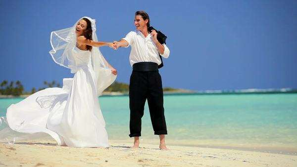 Attractive Caucasian couple laughing & dancing barefoot on the beach after their dream wedding Royalty-free stock video