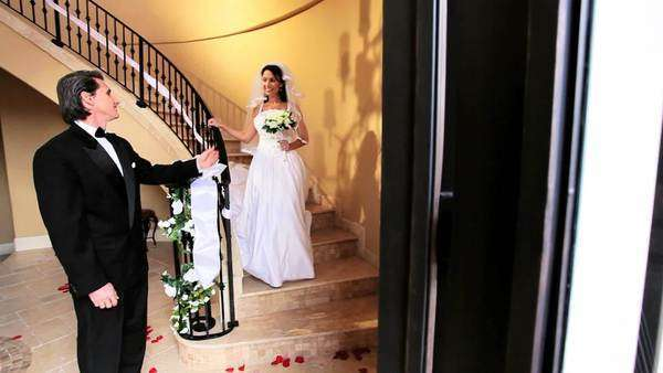 Bridegroom watching beautiful Caucasian bride wedding dress descending marble staircase Royalty-free stock video