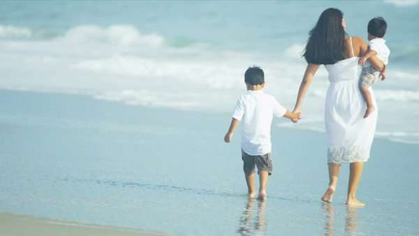Latin American young loving mother walking on beach with children shot on RED EPIC Royalty-free stock video