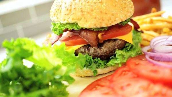 Cooked beef burger packed sesame seed bun topped bacon strips cheese salad vegetables served crisp French fries making classic bacon cheeseburger meal Royalty-free stock video