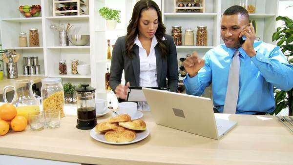 Modern African American professional couple working breakfast using wireless laptop tablet hearing news business success via smart phone call Royalty-free stock video
