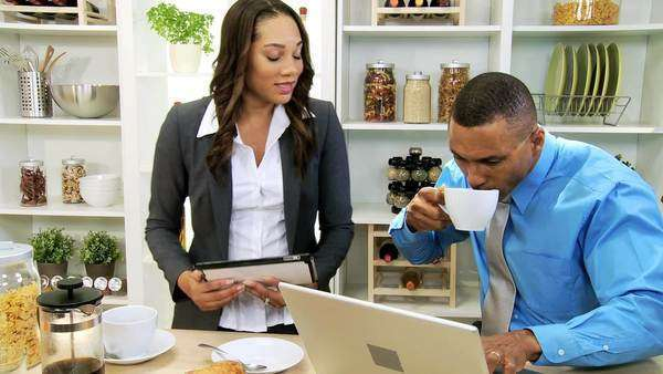 Ambitious young professional African American couple drinking breakfast coffee using wireless technology laptop tablet home kitchen counter Royalty-free stock video