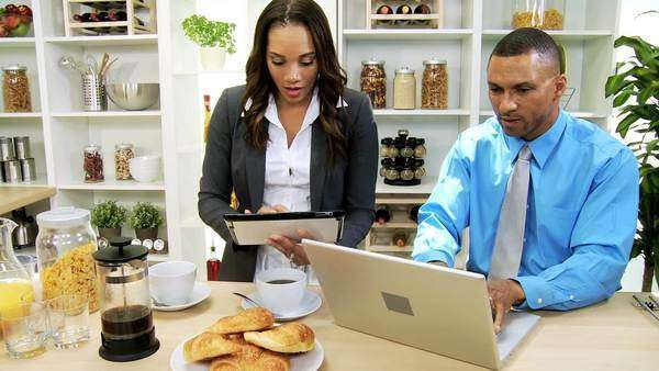 Modern African American professional couple working breakfast using wireless laptop touch screen tablet drinking coffee Royalty-free stock video