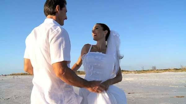 Bride & bridegroom having fun after their wedding on the beach filmed at 60FPS Royalty-free stock video