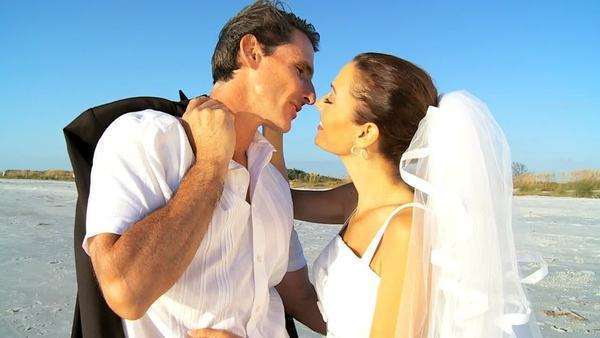 Bride & bridegroom sharing a kiss on the beach after their wedding ceremony filmed at 60FPS Royalty-free stock video