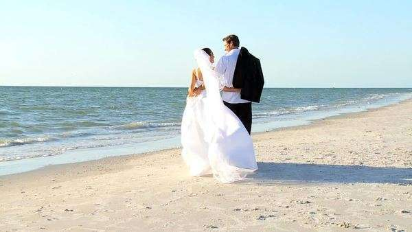 Bride & bridegroom walking on the beach after their wedding ceremony filmed at 60FPS Royalty-free stock video