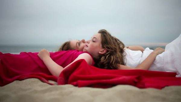 Profile of mother and daughter lying on beach pointing to sky Royalty-free stock video