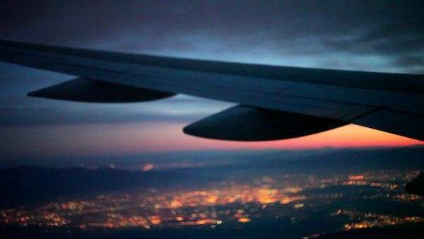 View of airplane wing while flying over city lights at sunset Royalty-free stock video