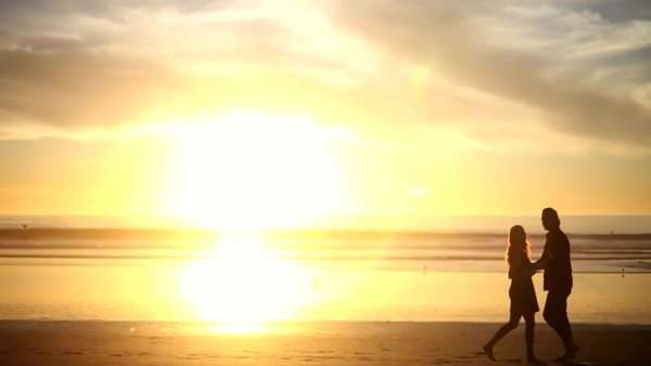 Couple running and spinning each other on beach at sunrise Royalty-free stock video