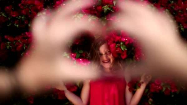 Young girl comes into focus through heart-shaped hands Royalty-free stock video