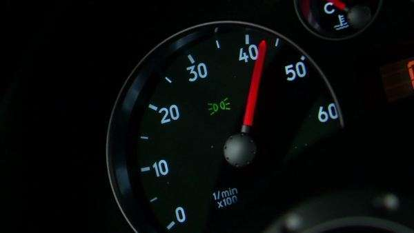 A close up of an RPM gauge. The dial goes up and down as the car engine is revved. Royalty-free stock video